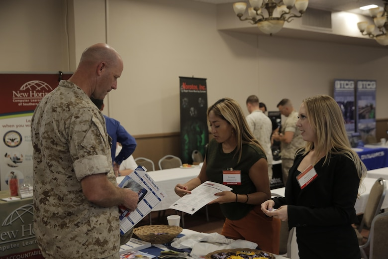 Master Gunnery Sgt. Steve Lowe, senior enlisted advisor, Marine Corps Tactics and Operations Group, speaks with Sharon Guervara, government sales manager, and Haley Scott, government contract manager, Divine Imaging Inc., about the different products and services the company offers at the Officers' Club during the Tactical and Technology Day Expo April 19, 2016. (Official Marine Corps photo by Pfc. Dave Flores/Released)