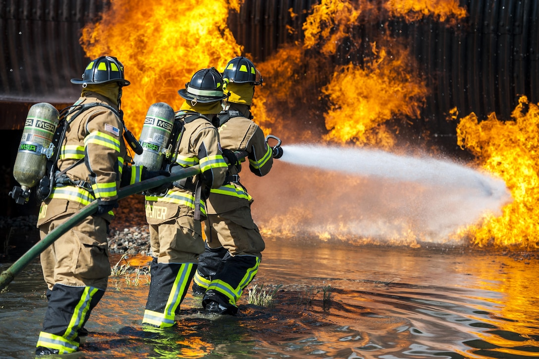 Firefighters from the 23d Civil Engineer Squadron and the Valdosta Fire Department put out an aircraft fire during aircraft live fire training, April 27, 2016, at Moody Air Force Base, Ga. Airmen extinguished a controlled propane fire, in order to simulate a jet fuel fire in an aircraft crash. (U.S. Air Force photo by Airman 1st Class Lauren M. Hunter/Released)