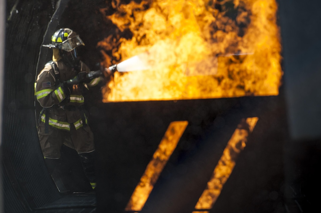 A firefighter from the 23d Civil Engineer Squadron puts out an engine fire during aircraft live fire training, April 27, 2016, at Moody Air Force Base, Ga. During the training exercise, Airmen practiced the proper techniques to extinguish a jet fuel fire in the case of an aircraft incident. (U.S. Air Force photo by Airman 1st Class Lauren M. Hunter/Released)