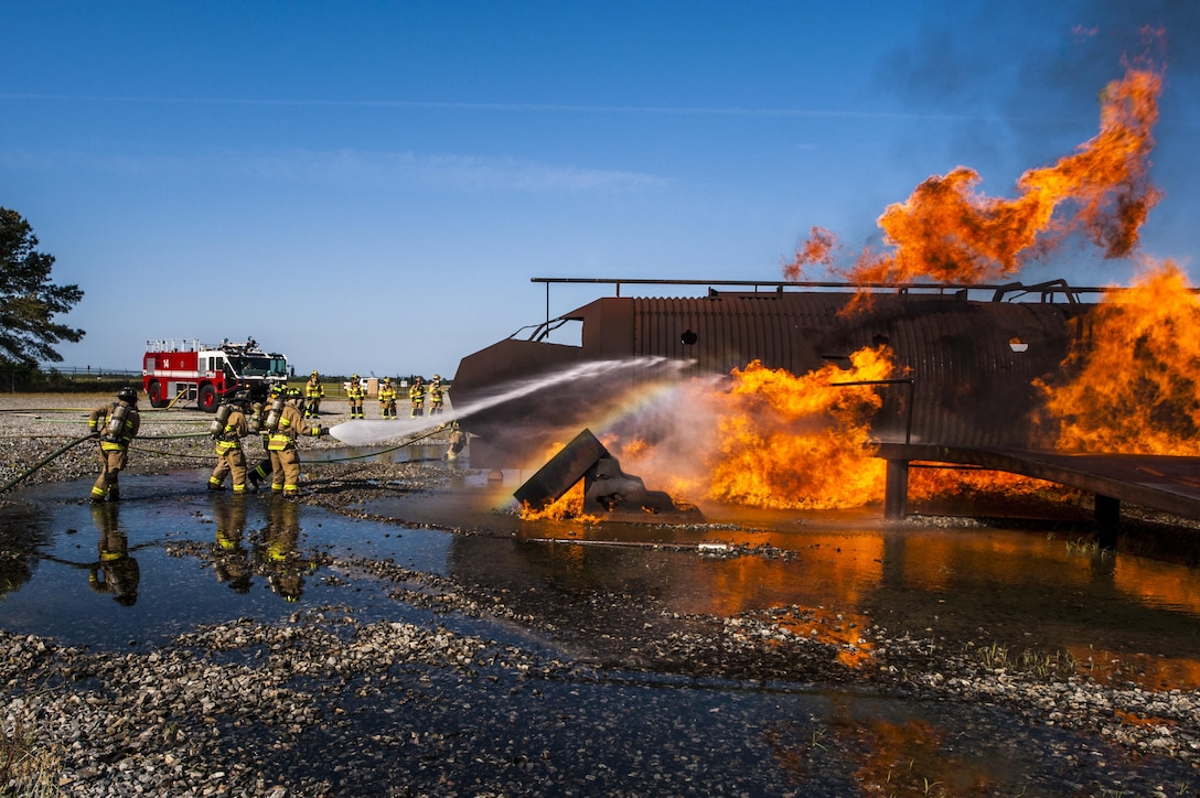 Firefighters from the 23d Civil Engineer Squadron and the Valdosta Fire Department extinguish a fire during aircraft live fire training, April 26, 2016, at Moody Air Force Base, Ga. Moody's firefighters maintain a working relationship with the VFD in order to know what to expect from each other when combatting a fire together in a real world situation. (U.S. Air Force photo by Airman 1st Class Lauren M. Hunter/Released)
