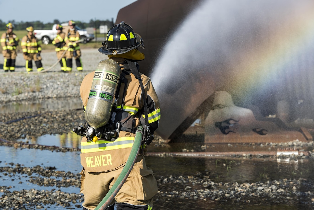 U.S. Air Force Tech. Sgt. Stephen Weaver, 23d Civil Engineer Squadron fire protection station chief, extinguishes an aircraft fire, April 26, 2016, at Moody Air Force Base, Ga. Moody's fire department teams up with the Valdosta Fire Department twice a year to remain proficient on procedures and techniques used to put out aircraft fires. (U.S. Air Force photo by Airman 1st Class Janiqua P. Robinson/Released)