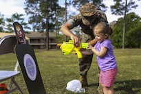 A Marine gives a girl a lesson on aiming at a target during Combat Logistics Regiment 2's Bring Your Sons and Daughters to Work Day at Camp Lejeune, N.C., April 28, 2016. The event helped to bolster the unit's morale and give families more time with one another. Marine Corps photo by Cpl. Dalton A. Precht