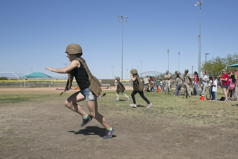 Combat Center children participate in a relay race while wearing flak jackets and kevlar helmets as part of the Lifestyle, Insights, Networking, Knowledge, and Skills annual Combined Arms Exercise for Kids at Felix Field April 20, 2016. (Official Marine Corps photo by Cpl. Thomas Mudd/Released)
