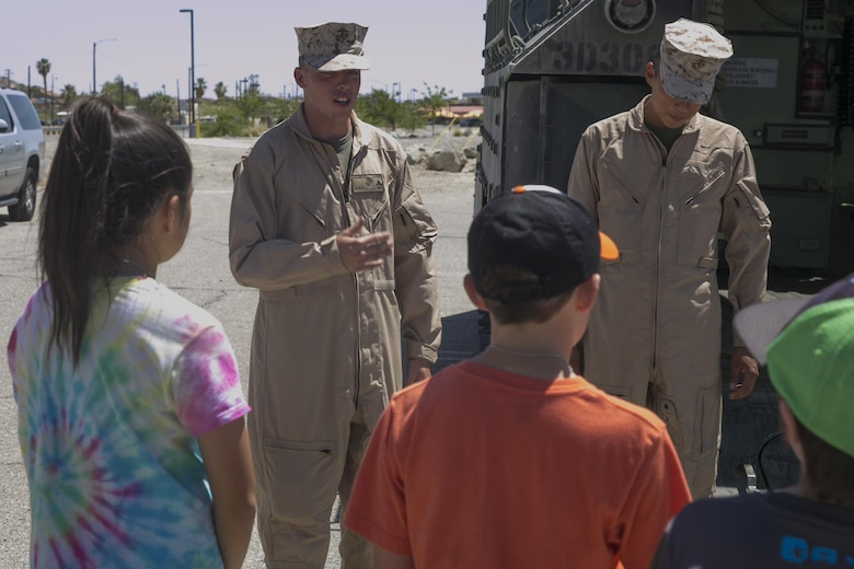 Lance Cpl. Seth Wyatt, vehicle commander, 3rd Assault Amphibian Battalion, teaches Combat Center children about the Amphibious Assault Vehicle P7/A1 as part of the Lifestyle, Insights, Networking, Knowledge, and Skills annual Combined Arms Exercise for Kids at Felix Field April 20, 2016. (Official Marine Corps photo by Cpl. Thomas Mudd/Released)