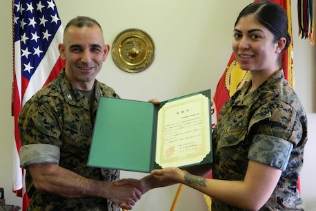 Col. George G. Malkasian, Camp Courtney commanding officer, thanks Cpl. Cristina Rivera for the contribution to build friendship with local community and handed her the letter of appreciation.