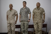 """U.S. Marine Corps Maj. Chad E. Craven, commanding officer, Delta Company, Communication Training Battalion, U.S. Air Force Lt. Col.  Russell """"Bones"""" Cook, squadron commander, 563 Operations Support Squadron, and Master Gunnery Sgt. Jerry Romero, senior enlisted advisor, Company D, CTB, stand at the position of attention during the playing of the national anthem during Craven's retirement ceremony at the base theater April 20, 2016. Craven retired after 24-years of honorable service. (Official Marine Corps photo by Cpl. Julio McGraw/Released)"""