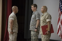 """U.S. Marine Corps Maj. Chad E. Craven, commanding officer, Delta Company, Communication Training Battalion, U.S. Air Force Lt. Col.  Russell """"Bones"""" Cook, squadron commander, 563 Operations Support Squadron, and Master Gunnery Sgt. Jerry Romero, senior enlisted advisor, Company D, CTB, stand at the position of attention for the reading of Craven's letter of appreciation from President Barack Obama  during Craven's retirement ceremony at the base theater April 20, 2016. Craven retired after 24-years of honorable service. (Official Marine Corps photo by Cpl. Julio McGraw/Released)"""