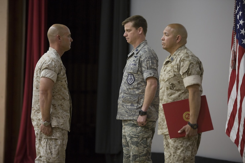 "U.S. Marine Corps Maj. Chad E. Craven, commanding officer, Delta Company, Communication Training Battalion, U.S. Air Force Lt. Col.  Russell ""Bones"" Cook, squadron commander, 563 Operations Support Squadron, and Master Gunnery Sgt. Jerry Romero, senior enlisted advisor, Company D, CTB, stand at the position of attention for the reading of Craven's letter of appreciation from President Barack Obama  during Craven's retirement ceremony at the base theater April 20, 2016. Craven retired after 24-years of honorable service. (Official Marine Corps photo by Cpl. Julio McGraw/Released)"