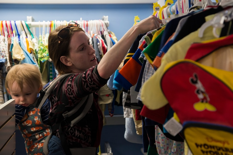 A shopper looks through clothing racks at the Chief Master Sgt. Gene Collins Airman's Attic April 12, 2016 at Scott Air Force Base, IllThe Airman's Attic not only serves military members E-5 and below, but they also serve their dependents. (U.S. Air Force photo by Airman 1st Class Gwendalyn Smith)