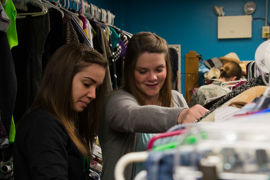 Shoppers look through clothing racks at the Chief Master Sgt. Gene Collins Airman's Attic April 12, 2016 at Scott Air Force Base, Ill. The Airman's Attic not only serves military members E-5 and below, but they also serve their dependents. (U.S. Air Force photo by Airman 1st Class Gwendalyn Smith)