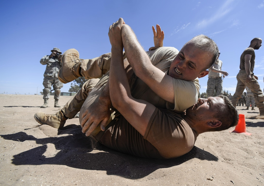 A U.S. Airman and a Royal Netherlands Army soldier wrestle after receiving a level two exposure to pepper spray as part of a nonlethal weapons class during exercise African Lion 16 in Tifnit, Morocco, April 23, 2016. The participants of the class had the opportunity to receive either a level one or two exposure before practicing nonlethal skills learned during the class. (U.S. Air Force photo/Senior Airman Krystal Ardrey)