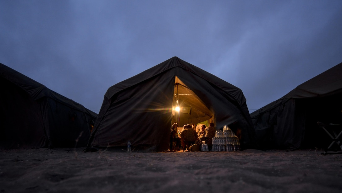 Military members participating in exercise African Lion 16 gather inside a tent at the end of the day in Tifnit, Morocco, April 23, 2016. Of the 11 nations participating in the annual exercise were a group of U.S. military members, Royal Moroccan Armed Forces members, Spanish Legion soldiers and Royal Netherlands Army soldiers. They lived in field conditions and participated in daily familiarization with other nations' tactics to improve interoperability. (U.S. Air Force photo/Senior Airman Krystal Ardrey)