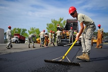 Airman 1st Class Bryan Daniel, a heavy equipment operator with the 823rd RED HORSE Squadron, sifts freshly laid asphalt to the proper depth at Hurlburt Field, Fla., April 20, 2016. As part of a two-week milling and paving training course, more than 20 Airmen from across the globe participated by laying asphalt to repair a parking lot. (U.S. Air Force photo/Airman 1st Class Joseph Pick)