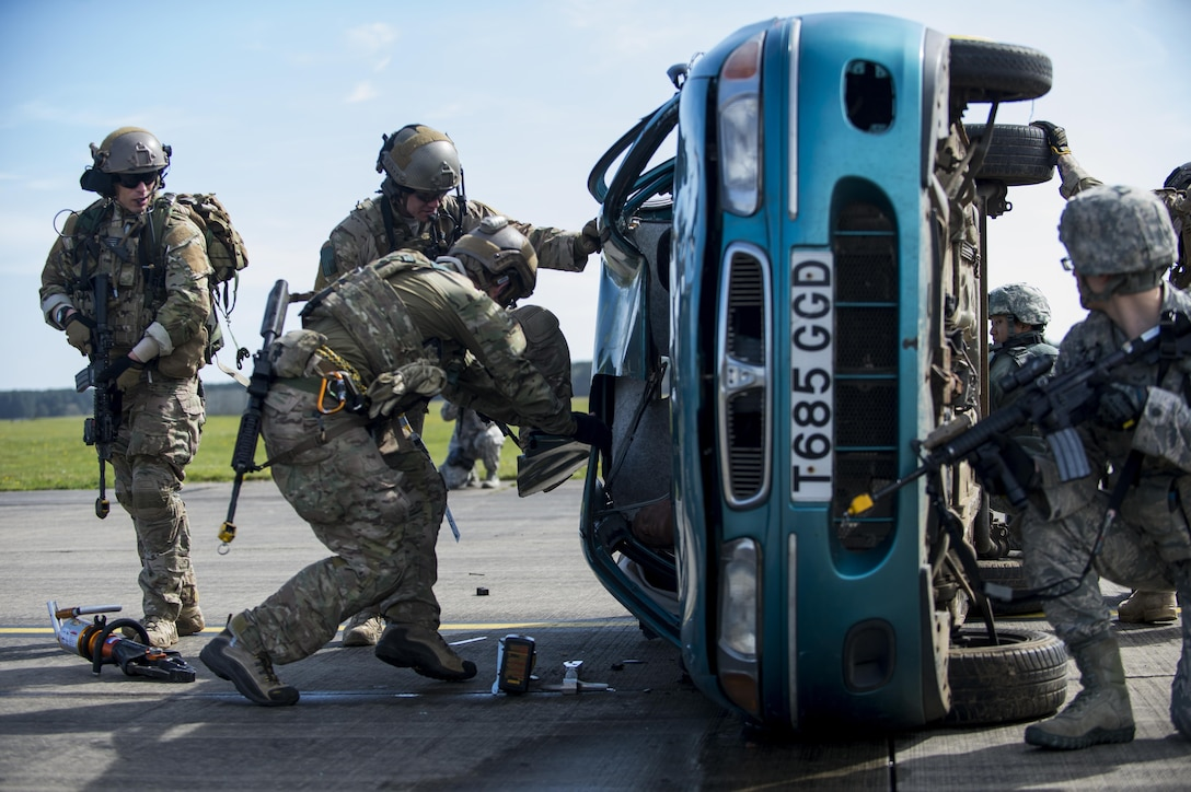 Pararescuemen assigned to the 57th Rescue Squadron use the Jaws of Life to tear apart a vehicle's roof to remove a mock victim during a combat search and rescue demonstration at Royal Air Force Lakenheath, England, April 21, 2016. Pararescuemen and members of the 48th Security Forces Squadron demonstrated the rescue during a Chief of Staff of the Air Force Civic Leader Program visit. (U.S. Air Force photo/Staff Sgt. Emerson Nuñez)