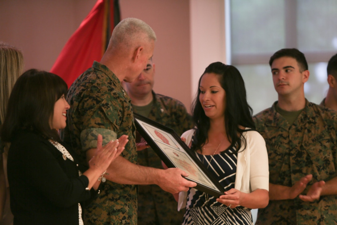 Major Gen. Brian Beaudreault, commanding general of 2nd Marine Division, presents an award for the volunteers of 10th Marine Regiment to Jessica Gay, the 10th Marines family readiness advisor, for organizing and volunteering at numerous events during a ceremony held at Camp Lejeune, N. C., April 27, 2016. The family readiness advisor's job is to assist the family readiness officer with any tasks and to provide extra support for the families in their units. (U.S. Marine Corps photo by Cpl. Melodie Snarr/Released)
