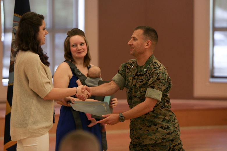 Lieutenant Col. Kenneth Lee, the commanding officer for 2nd Transportation Support Battalion, presents volunteer awards to Alex Renegar and Caitlyn Loomis, volunteers for 2nd Transportation Support Battalion and spouses of Marines in the battalion, during a ceremony held at Camp Lejeune, N. C., April 27, 2016. Lee said Renegar and Loomis always find time to give back to the unit, despite the workload and schedule of their Marine husbands within the battalion. (U.S. Marine Corps photo by Cpl. Melodie Snarr/Released)