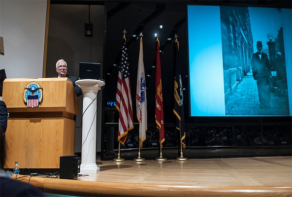 John Koenigsberg addresses an audience gathered in the Building 20 auditorium during the Defense Supply Center Columbus Days of Remembrance event. Koenigsberg shared his personal story of survival and perseverance during the Holocaust, and stressed the importance of honoring those who lost their lives by keeping their memory alive.