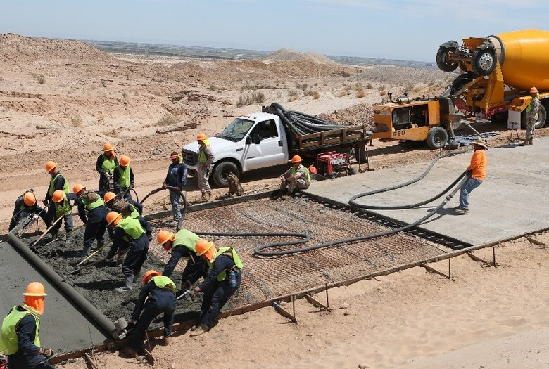 U.S. Marines with 7th Engineer Support Battalion assist in pouring out concrete during a road improvement project with Joint Task Force North in El Centro, Calif., April 19, 2016. For the last two months, the Marines have been processing and leveling dirt to improve the road's quality as well as constructing low-water crossings to maintain the integrity of the road during wet conditions. (U.S. Marine Corps photo by Cpl. Carson Gramley/released)