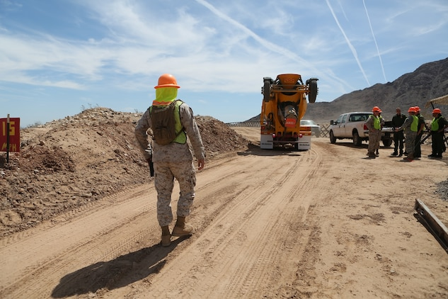 U.S. Marine Staff Sgt. Carlos Rodriguez guides a concrete truck backward during a road improvement project with Joint Task Force North in El Centro, Calif., April 19, 2016. Rodriguez is the staff non-commissioned officer in charge of Headquarters and Support Company, 7th Engineer Support Battalion. For the last two months, the Marines have been processing and leveling dirt to improve the road's quality as well as constructing low-water crossings to maintain the integrity of the road during wet conditions. (U.S. Marine Corps photo by Cpl. Carson Gramley/released)