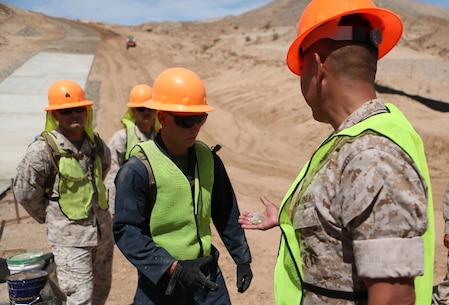 U.S. Marine Col. Ladaniel Dayzie presents a Marine from 7th Engineer Support Battalion with a challenge coin in El Centro, Calif., April 19, 2016. Dayzie is the deputy commander of Joint Task Force North in El Centro. Marines with 7th ESB assisted in a road improvement project with JTF-N during the months of March and April. During the project, the Marines have been processing and leveling dirt to improve the road's quality as well as constructing low-water crossings to maintain the integrity of the road during wet conditions. (U.S. Marine Corps photo by Cpl. Carson Gramley/released)