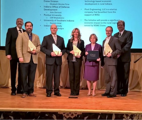 FLC State and Local Economic Development Award winners, left to right:  Paul Zielinski, NIST/FLC Chair; Norman Hedges, IU Law Clinic; Cliff Wojtalewicz, Purdue University; Brooke Pyne, NSWC Crane ORTA/T2 Program Manager; Dottie Vincent, ONR T2 Director; John Dement, IODD; and Mark Reeves, Oak Ridge National Lab/FLC Vice-Chair