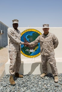 U.S. Marine Corps Sgt. Maj. Reginald Robinson, left, the former sergeant major of the Special Purpose Marine Air-Ground Task Force Crisis Response-Central Command (SPMAGTF-CR-CC), shakes hands with Sgt. Maj. Chuong Nguyen, the sergeant major of the incoming SPMAGTF-CR-CC, in an undisclosed location, Southwest Asia, April 23, 2016. (U.S. Marine Corps photo by Cpl. Trever A. Statz/Released)