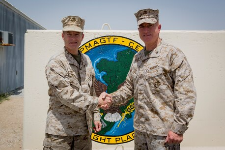 U.S. Marine Corps Col. William Mccollough, left, the former commanding officer of the Special Purpose Marine Air-Ground Task Force Crisis Response-Central Command (SPMAGTF-CR-CC), shakes hands with Col. Kenneth Kassner, the commanding officer of the incoming SPMAGTF-CR-CC, in an undisclosed location, Southwest Asia, April 23, 2016. (U.S. Marine Corps photo by Cpl. Trever A. Statz/Released)