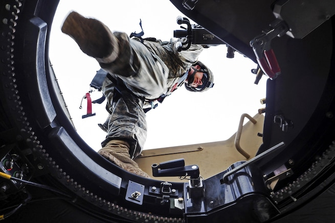 A paratrooper steps over the opening of the gunner's hatch while at an M2 .50 caliber machine gun range at Joint Base Elmendorf-Richardson, Alaska, April 26, 2016. Air Force photo by Justin Connaher
