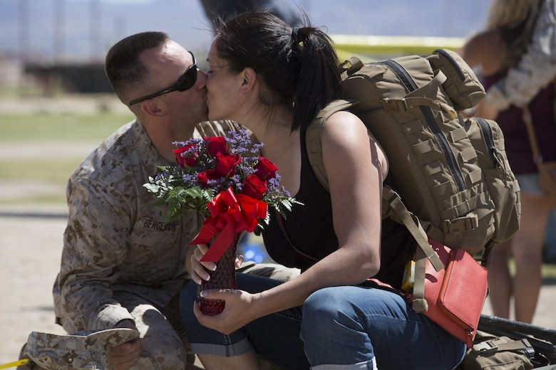 Gunnery Sgt. Jeremiah Bergeron, platoon sergeant, 1st Battalion, 7th Marine Regiment, kisses his fiancée, Amneri Vazquez, during the battalion's homecoming at Del Valle Field April 23, 2016. 1/7 was deployed as part of Special Purpose Marine Air Ground Task Force-Crisis Response-Central Command 16.1. (Official Marine Corps photo by Cpl. Julio McGraw/Released)