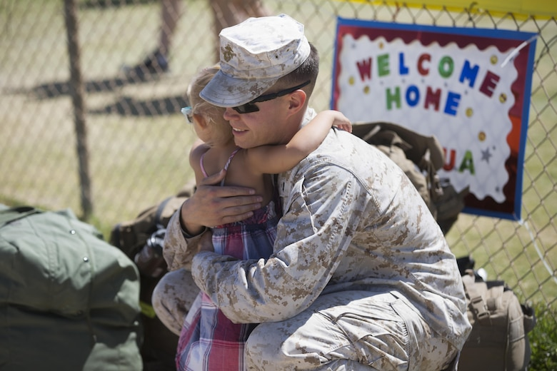 Staff Sgt. William Simpson, electronic maintenance technician, 1st Battalion, 7th Marine Regiment, embraces his 3-year-old daughter, Hannah, during the battalion's homecoming at Del Valle Field April 23, 2016. 1/7 was deployed as part of Special Purpose Marine Air Ground Task Force-Crisis Response-Central Command 16.1. (Official Marine Corps photo by Cpl. Julio McGraw/Released)