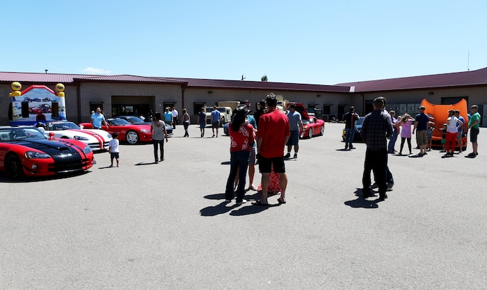 Marines and their families look at a line-up of show cars during a family day hosted by 1st Explosive Ordnance Disposal Company, 7th Engineer Support Battalion, 1st Marine Logistics Group, aboard Camp Pendleton, Calif., April 23, 2016. Marines with 1st EOD Co. hosted the Viper Club of Southern California for the day as a part of their celebration which included food, family activities, and various show cars. (U.S. Marine Corps photo by Cpl. Carson Gramley/released)