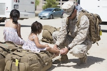 Sgt. Jonathan Lopez, rifleman, 1st Battalion, 7th Marine Regiment, adjusts his daughter's sandal during the battalion's homecoming at Del Valle Field April 23, 2016. 1/7 was deployed as part of Special Purpose Marine Air Ground Task Force-Crisis Response-Central Command 16.1. (Official Marine Corps photo by Cpl. Julio McGraw/Released)
