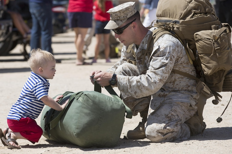 Barret, 2, son of Capt. Sean Wetherill, logistics officer, 1st Battalion, 7th Marine Regiment, helps his father gather his belongings during the battalion's homecoming at Del Valle Field April 23, 2016. 1/7 was deployed as part of Special Purpose Marine Air Ground Task Force-Crisis Response-Central Command 16.1. (Official Marine Corps photo by Cpl. Julio McGraw/Released)