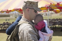 Staff Sgt. Darrell Wills, data network specialist, 1st Battalion, 7th Marine Regiment, greets his 2-month-old daughter, Katie, during the battalion's homecoming at Del Valle Field April 23, 2016. 1/7 was deployed as part of Special Purpose Marine Air Ground Task Force-Crisis Response-Central Command 16.1. (Official Marine Corps photo by Cpl. Medina Ayala-Lo/Released)