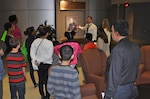 Leading a tour of the McNamara Headquarters Complex, Mark Simon shows kids and parents a portrait of  Lt. Gen. Andrew T. McNamara, first director of the Defense Logistics Agency, during 'Take You Daughters and Sons to Work Day' April 28.