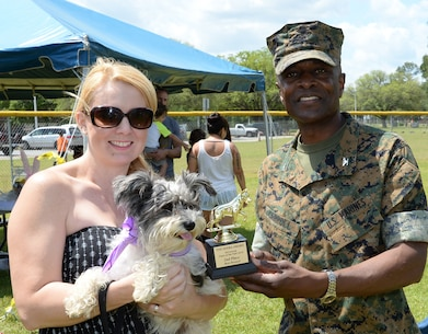 Angel, a Miniature Schnauzer held by her owner Amy Lawson, places second in the best dressed competition at the Paws at the Park event aboard Marine Corps Logistics Base Albany's Crouch Field, April 23. Col. James C. Carroll III, commanding officer, MCLB Albany, presented the awards.