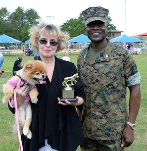 "Chloe, a 7-year-old Pomeranian held by her owner Jane Fiore, defends her first place title in the Paws at the Park best dressed category at Marine Corps Logistics Base Albany's Crouch Field, April 23. Chloe wore a pink T-shirt that read ""Rainbows makes me smile."" Col. James C. Carroll III, commanding officer, MCLB Albany, presented the awards."