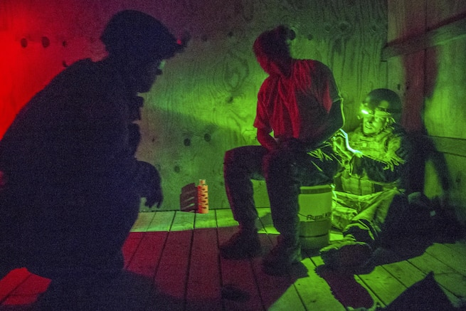 Army Spc. Jason Green, left, talks to a hostage role player while Staff Sgt. Jesse Harris works to disarm explosives during a hostage rescue scenario for the 52nd and 111th Ordnance Group Joint Team of the Year 2016 competition at a training center in Greenville, Ky., April 28, 2016. The weeklong event tests teams in various scenarios they may encounter in situations around the world. Green is assigned to the 49th Ordnance Company, 184th Ordnance Battalion. Army Photo by Staff Sgt. Brian Kohl
