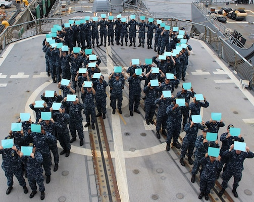 Sailors on board the Ticonderoga-class guided-missile cruiser USS Chancellorsville (CG 62) gather on the flight deck to form a teal ribbon, in recognition of  Sexual Assault Prevention (SAPR) Month. The teal ribbon signifies the U.S. Navy's zero tolerance policy against sexual assault.