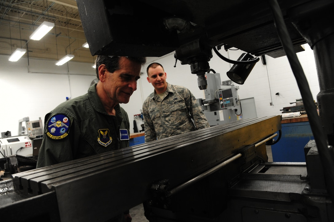 Dean Kamen, the FIRST Robotics founder, left, and U.S. Air Force Senior Airman Matthew Ebarb, a 509th Maintenance Squadron aircraft metals technician, view a milling machine at Whiteman Air Force Base, Mo., April 26, 2016. Kamen met Airmen and FIRST Robotics alumni during his visit and received an incentive flight in a B-2 Spirit. The U.S. Air Force and FIRST Robotics share an interest in developing youth into future leaders through exposure to education in science, technology, engineering and mathematics. (U.S. Air Force photo by Airman 1st Class Keenan Berry)