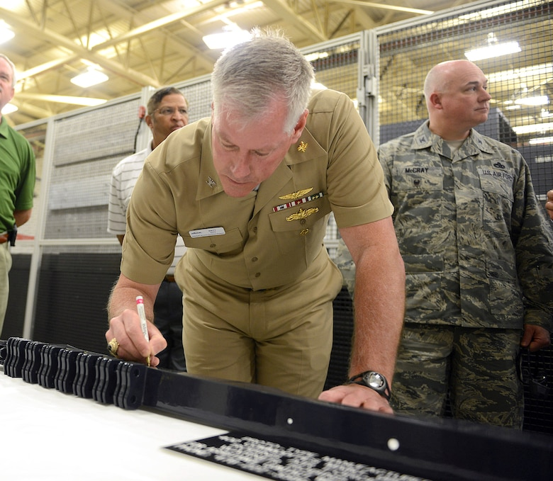 Capt. Matt Ott, Aviation Operations director with Naval Supply Systems Command, autographs a prototype manufactured by the 402nd Commodities Maintenance Group. Officials from the Navy and NORDAM, a global aerospace manufacturing and repair company, visited the 402nd CMXG, April 26, 2016, to celebrate a partnership that was formed in 2014 to manufacture F/A-18 outer wing panel spars to support NORDAM's F/A-18 Legacy Hornet wing repair lines.. (U.S. Air Force photo by Tommie Horton)