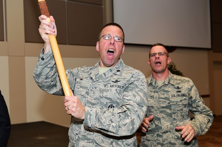 Lt. Col. Timothy Bos, 460th Operations Support Squadron commander, and Chief Master Sgt. Joseph Stratil, 460th Operations Group superintendent,  yell the Operations Group chant after winning the spirit stick during the 460th Space Wing first quarter award ceremony April 28, 2016, at the Leadership Development Center on Buckley Air Force Base, Colo. The spirit stick is awarded to the group who shows the most esprit de corps during the ceremony. (U.S. Air Force photo by Senior Airman Racheal E. Watson/Released)