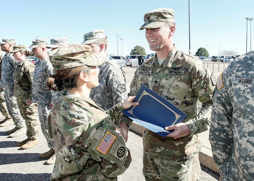 U.S. Army Spc. Brian Carter, 743d Military Intelligence Battalion Alpha company, receives a certificate from Col. Michele Bredenkamp, 704th Military Intelligence Battalion brigade commander, during a Space Badge presentation ceremony March 10, 2016, at Buckley Air Force Base, Colo. The badge was formerly called the Air Force Space Badge, but Air Force was dropped from the name because the Army and Air Force personnel are now eligible, calling the badge the Space Badge. (U.S. Army photo by Sgt. Kristopher Dimond/Released)