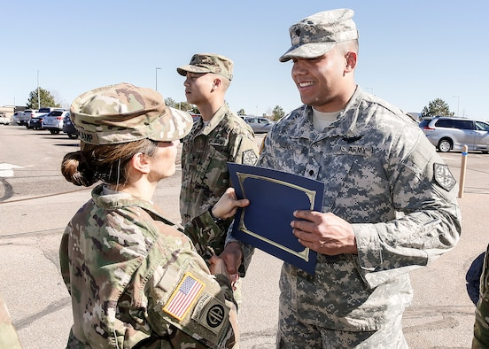 U.S. Army Col. Michele Bredenkamp, 704th Military Intelligence Battalion brigade commander, gives Spc. Kevin Lewis, 743d Military Intelligence Battalion Alpha company, his Space Badge certificate March 10, 2016, at Buckley Air Force Base, Colo. The Space Badge can be awarded to active Army, Army Reserve and National Guard Soldiers who successfully complete appropriate space-related training and attain the required Army space cadre experience. There are three levels of the Space Badge: basic, senior and master. (U.S. Army photo by Sgt. Kristopher Dimond/Released)
