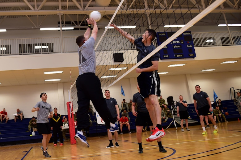 U.S. Army Spc. Howie Kim, 743d Military Intelligence Battalion signals analyst, blocks a spike by U.S. Army Sgt. David Perez, 743d Military Intelligence Battalion S3 training, April 27, 2016, at the Buckley Fitness Center on Buckley Air Force Base, Colo. The tournament consisted of three teams competing for two days with the winning team walking away with a trophy and bragging rights. (U.S. Air Force photo by Airman 1st Class Gabrielle Spradling/Released)