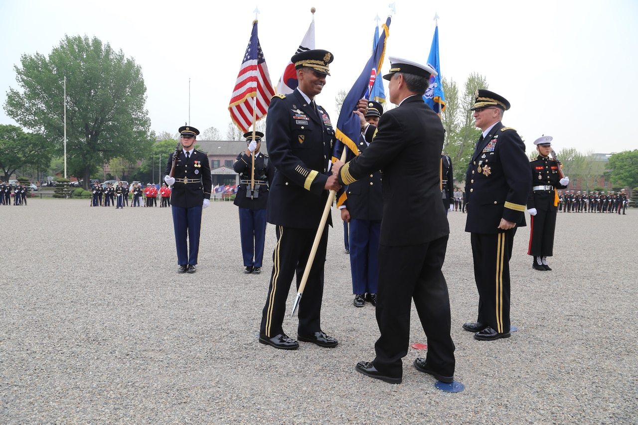 Gen. Vincent k. Brooks Takes the U.S. Forces Korea colors from Adm. Harry B. Harris, the commander of Pacific Command during a change of command ceremony in which Brooks took command of United Nations Command, Combined Force Command and U.S. Forces Korea.