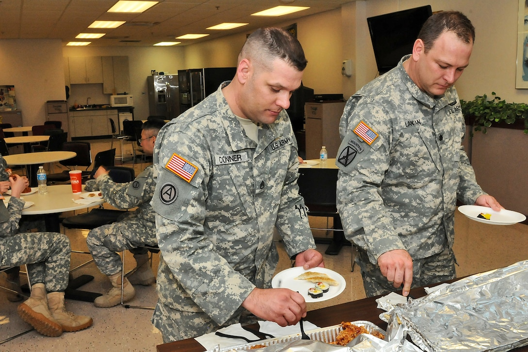 Staff Sgt. Joshua Conner, Training Sergeant, 85th Support Command and Lt. Col. Craig Lanigan, Alcohol and Drug Control Officer, 85th Support Command, sample Asian dishes provided by a local vendor in Arlington Heights, Ill., May 2. The dishes were a part of an Asian American and Pacific Islander Heritage Month observance conducted by the 85th Support Command's Equal Opportunity office during the command's battle assembly weekend training. (U.S. Army photo by Sgt. Aaron Berogan/Released)