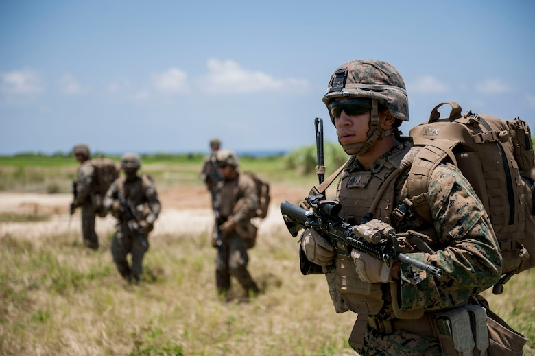 U.S. Marine Corps Cpl. James Ellis, Golf Company, 2nd Battalion, 2nd Marine Regiment squad leader assigned to Marine Corps Base Camp Lejeune, N.C., leads his fire team toward an objective during an airfield seizure exercise July 20, 2016, at Iejima airfield, Japan. Ellis and other Marines of Golf Company performed a simulated airfield seizure at Iejima to test their capability for a long-range joint operation with the U.S. Air Force 353rd Special Operations Squadron assigned to Kadena Air Base, Japan. (U.S. Air Force Photo by Senior Airman Peter Reft)