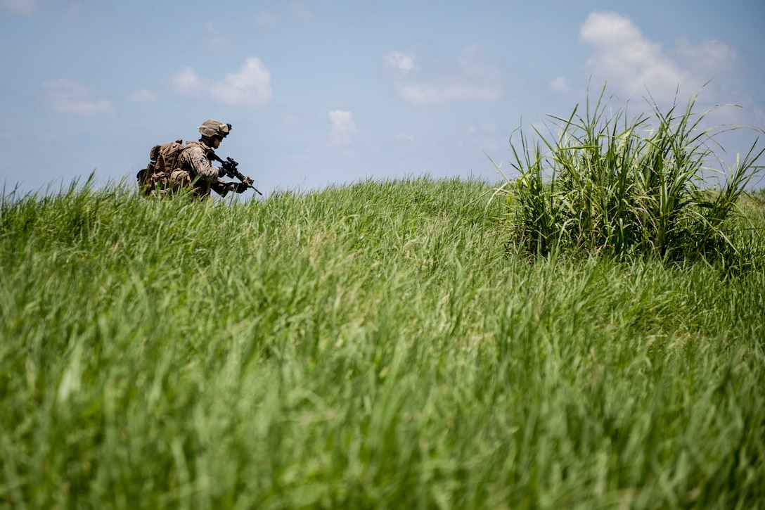 A U.S. Marine Corps rifleman assigned to Golf Company, 2nd Battalion, 2nd Marine Regiment, Marine Corps Base Camp Lejeune, N.C., navigates terrain during an airfield seizure exercise July 20, 2016, at Iejima airfield, Japan. Golf Company conducted their first long-range airfield seizure exercise with support from the Marine Medium Tiltrotor Squadron 265, Marine Corps Air Station Futenma, Japan and the U.S. Air Force 353rd Special Operations Group, Kadena Air Base, Japan. (U.S. Air Force Photo by Senior Airman Peter Reft)