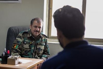 Afghan Air Force Lt. Col. Yaqubi Munir, lead recruiting officer, speaks to an interpreter at Kabul Air Wing, Afghanistan, Aug. 1, 2016. The AAF recruiters have a strong partnership with U.S. Airmen from Train, Advise, Assist Command-Air (TAAC-Air), and the two organizations are constantly fine-tuning the process to get the best and brightest young Afghans into the AAF. (U.S. Air Force photo by Tech. Sgt. Christopher Holmes)